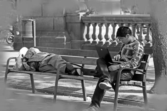 """Foto 1 – PRIMER PREMIO  • Autor: M. Sergio López Conde • Descripción de la obra: En la fotografía, titulada """"Contrastes"""", podemos observar en un mismo banco a una persona trabajando con su portátil, y quizás conectada a internet, junto a una persona sin hogar. La imagen llama la atención sobre el contraste entre clases sociales, demasiado corriente en el centro de cualquier ciudad, en esta ocasión Barcelona."""