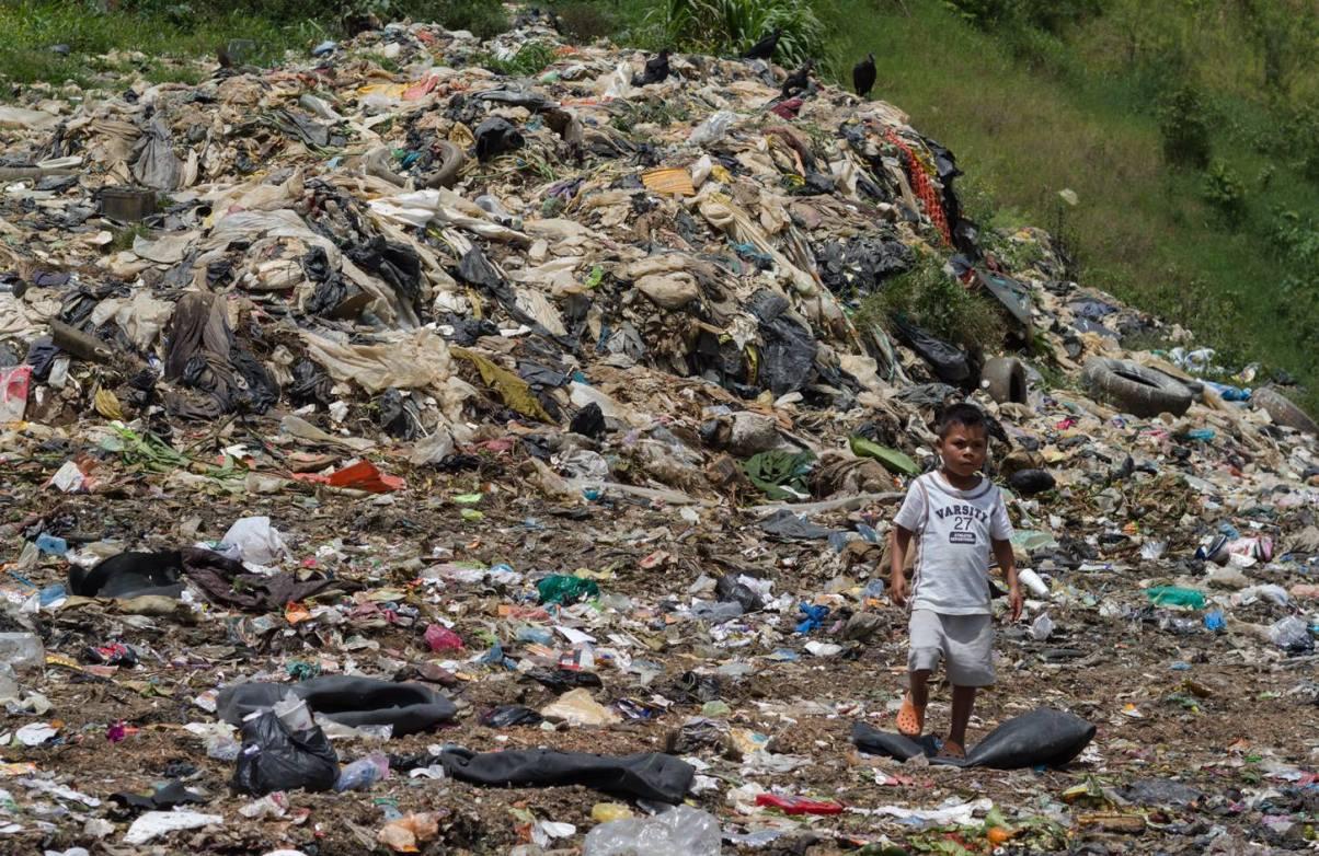 Foto 5 – FINALISTA • Autora: Alicia Petrashova • Descripción de la obra: El vertedero de Cobán no deja a nadie indiferente. En un lejano punto del mapa, la región de Alta Verapaz de Guatemala, esconde realidades y verdades tan duras como esta. Familias enteras trabajan reciclando la basura, al tiempo que viven en situación de exclusión social. La escena que se observa en la fotografía es la habitual de un sábado, una triste cotidianidad en la que las familias reciben el almuerzo donado por parte de una asociación local. No se trata de beneficencia, sino de una estrategia de acercamiento para promover el empoderamiento y la escolarización