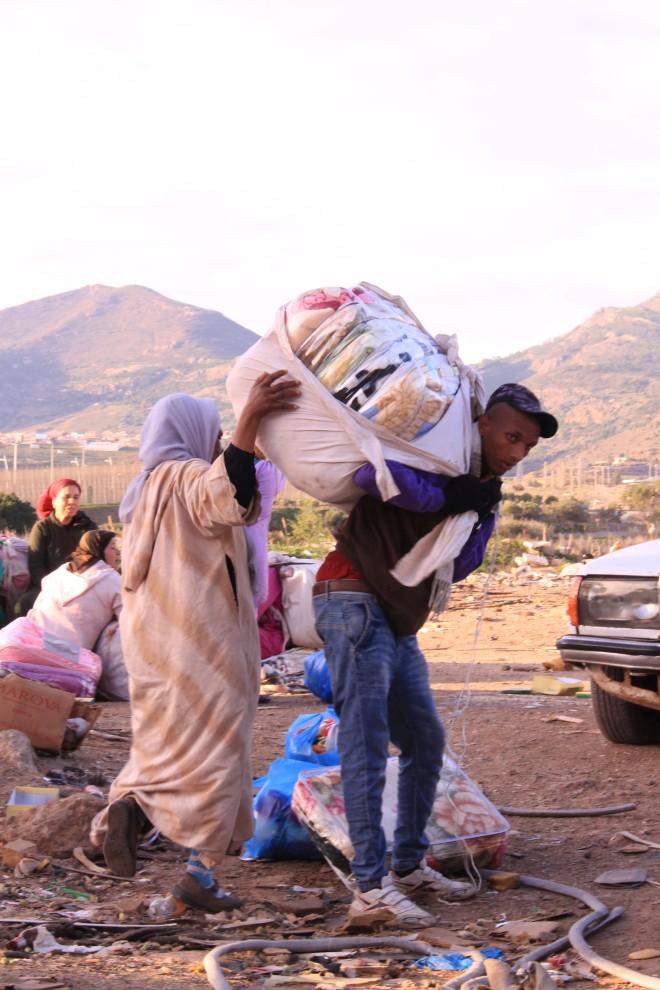 Título: Con la pobreza a la espalda Descripción: En las inmediaciones de la frontera de Beni Enzar de Melilla preparándose para pasar a Marruecos. Este es día a día de miles de personas, sobre todo mujeres, que cargan en sus espaldas con el peso de la pobreza y la exclusión social de un mundo que los rechaza. Autora: