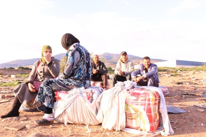 Título: Al mal tiempo buena cara Descripción: un grupo de porteadores de mercancías del contrabando diario entre España y Marruecos en Melilla, disfrutando del solecito de otoño.  Autora: Mª Cristina García